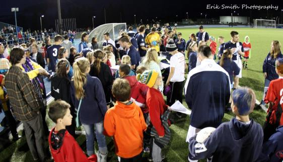 Shadow players sign autographs after the match. (Erik Smith)